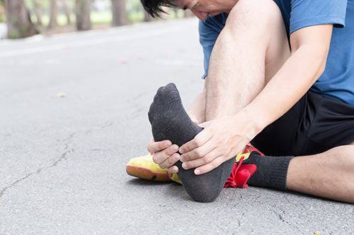 Plantar Fasciitis | photo of runner rubbing the arch of his foot