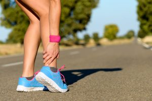 Female Runner grabbing her Achilles | Atlanta Podiatry
