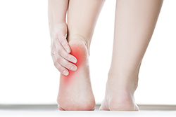 photo of woman holding her heel in pain | prp treatment