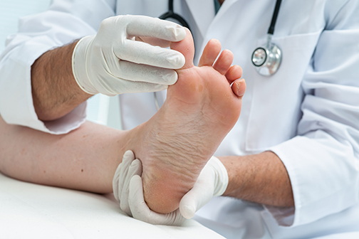 photo of a podiatrist examining a big toe | American Foot & Leg Specialists