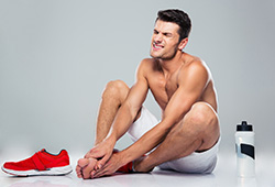 portrait of a fitness man with foot pain | American Foot & Leg Specialists