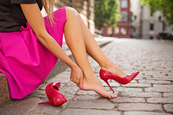 photo of woman holding her heel