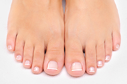 female feet with a French pedicure | American Foot & Leg Specialists