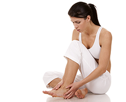 photo of a brunette woman holding her feet | American Foot & Leg Specialists