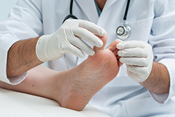 photo of podiatrist examining a foot | American Foot & Leg Specialists
