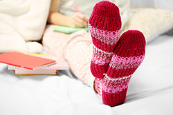 photo of female feet in woolen maroon socks on the bed