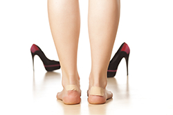 photo of woman with band aid on her heels due to blisters | American Foot & Leg Specialists