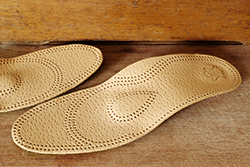photo of an orthopedic arch support made from leather on a wooden ground
