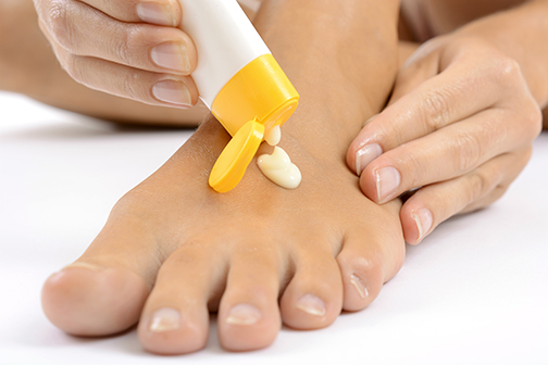 up close photo of lotion being applied to a foot