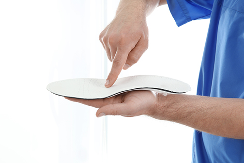 close up photo of a male orthopedist with insole on white background