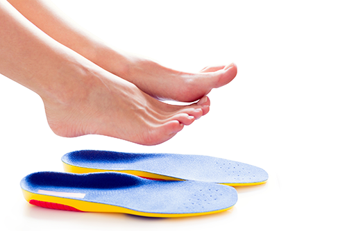 Foot Care Center | photo of two feet above a pair of insoles
