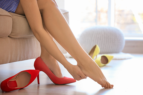 heel pain | photo of woman siiting with show off holding heel in pain