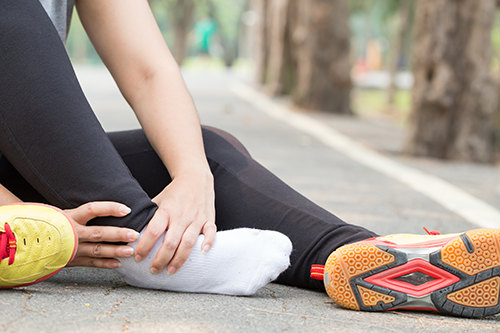 Plantar Fasciitis | photo of runner sitting and holding foot in pain